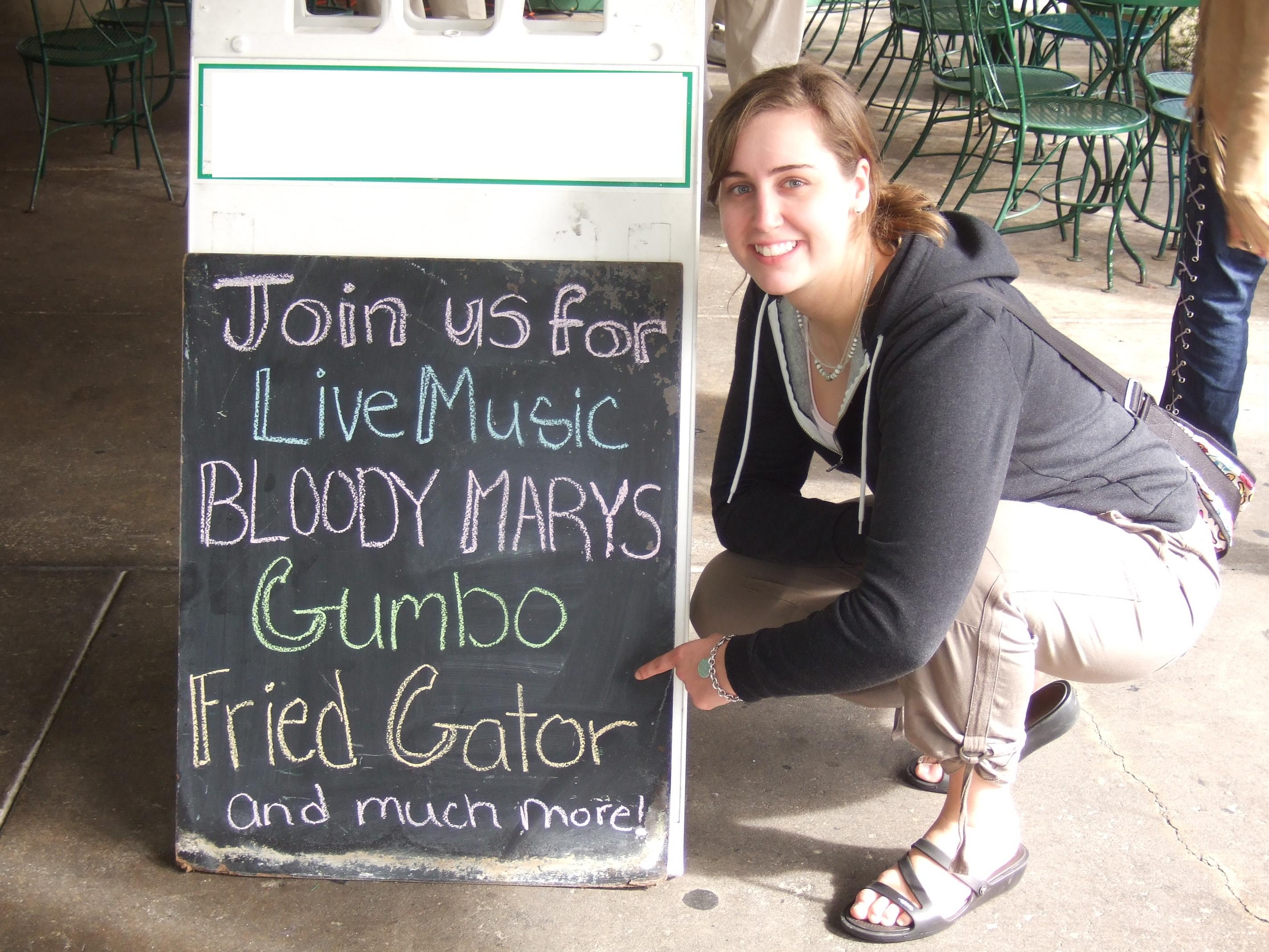 A menu board listing blood marys, gumbo, and fried gator