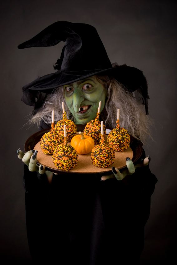 A witch holding a platter of candy apples