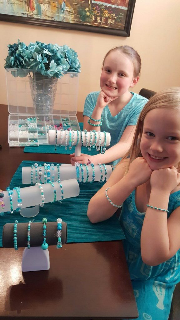Danica and Delaney wearing their handmade teal bead bracelets