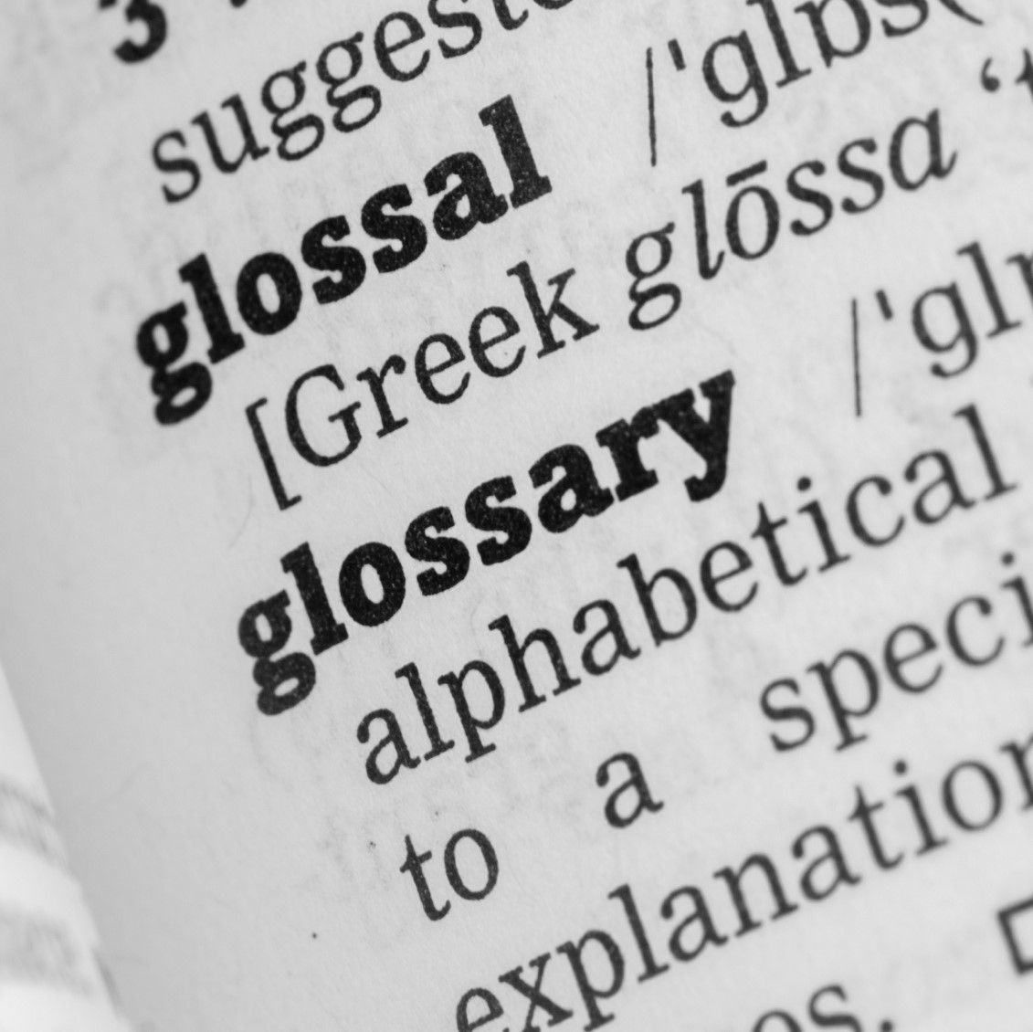 Dictionary, single word close up of the word glossary.