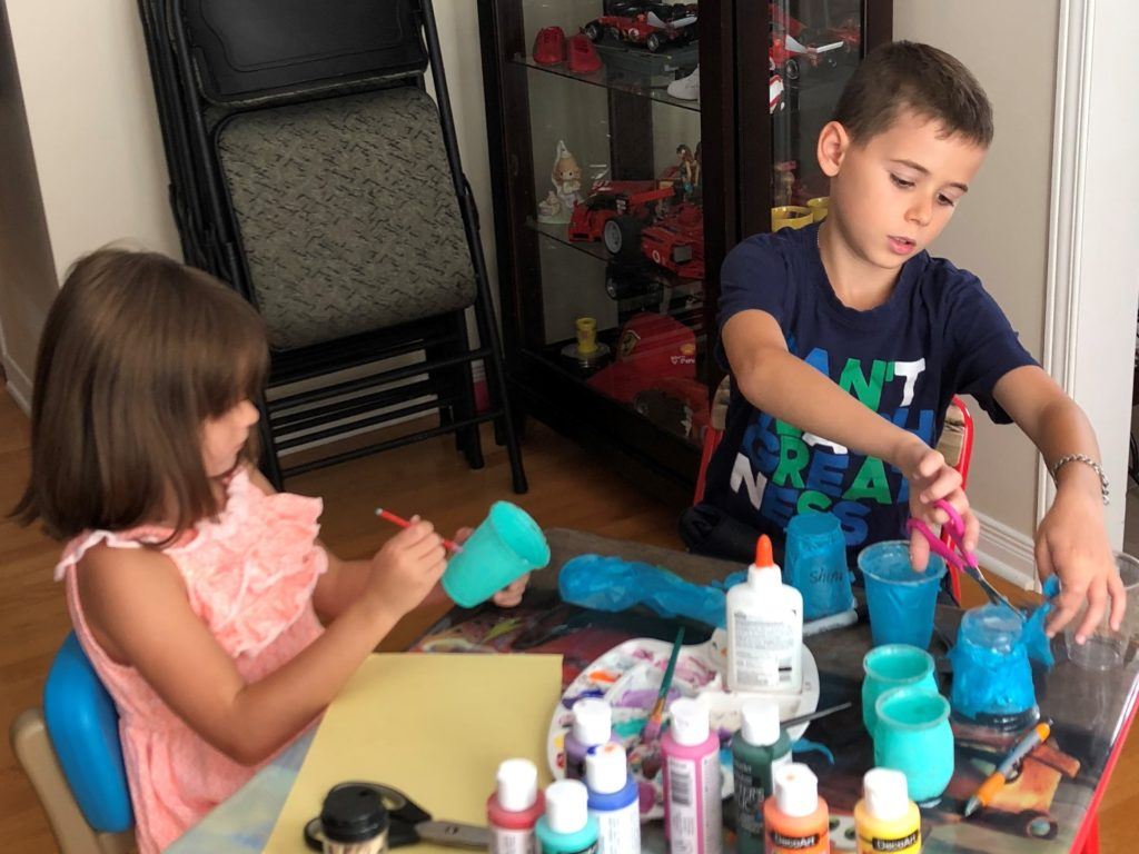 Adriana and Christian painting and making teal light crafts