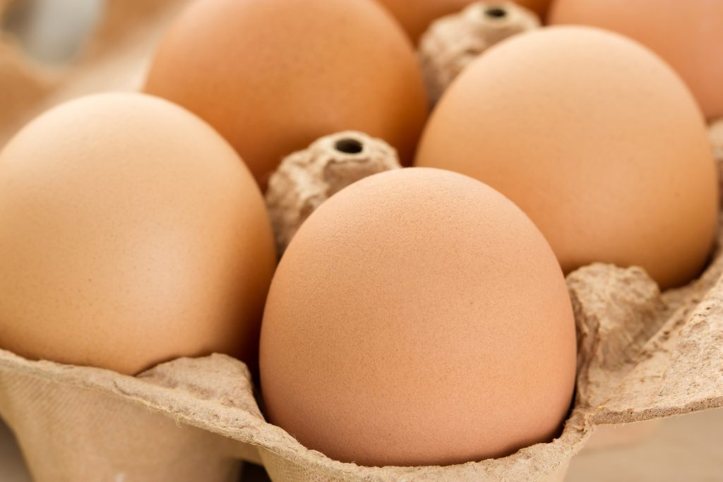 Close-up of brown eggs in egg box