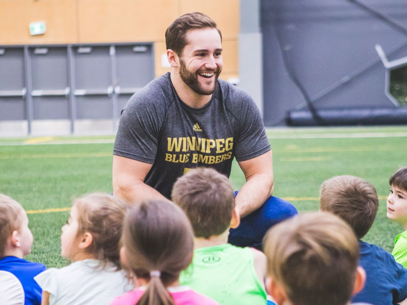 Thomas Miles talking with a group of children on a football field