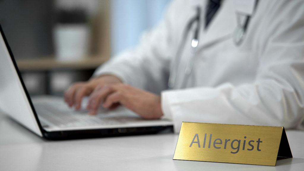 Male allergist prescribing medication in clinic, keeping records, health care