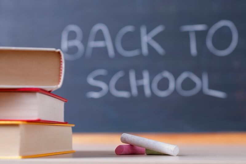 "Stack of books in front of a chalkboard that reads ""Back to school"""
