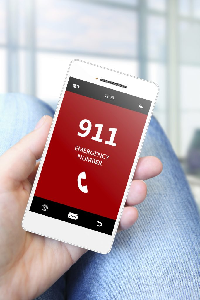 hand holding mobile phone with emergency number 911.