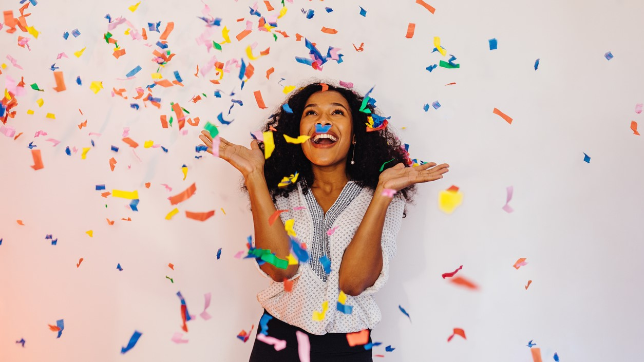 Young woman standing indoors under colorful confetti