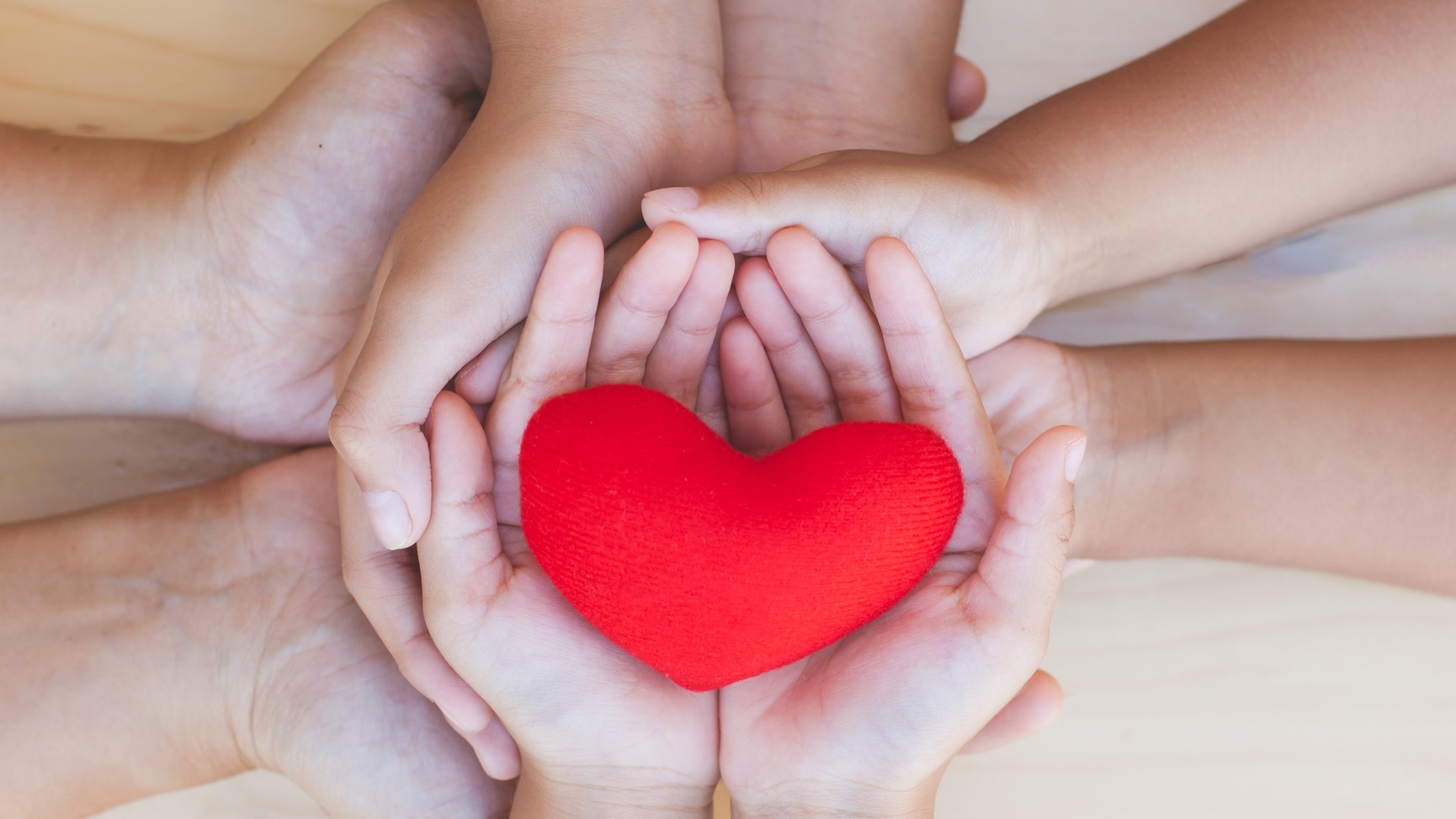 Red heart in parent and children holding handsFamily and friend stack hands with red heart