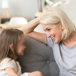 Little granddaughter talking with attentive grandmother, sitting on sofa
