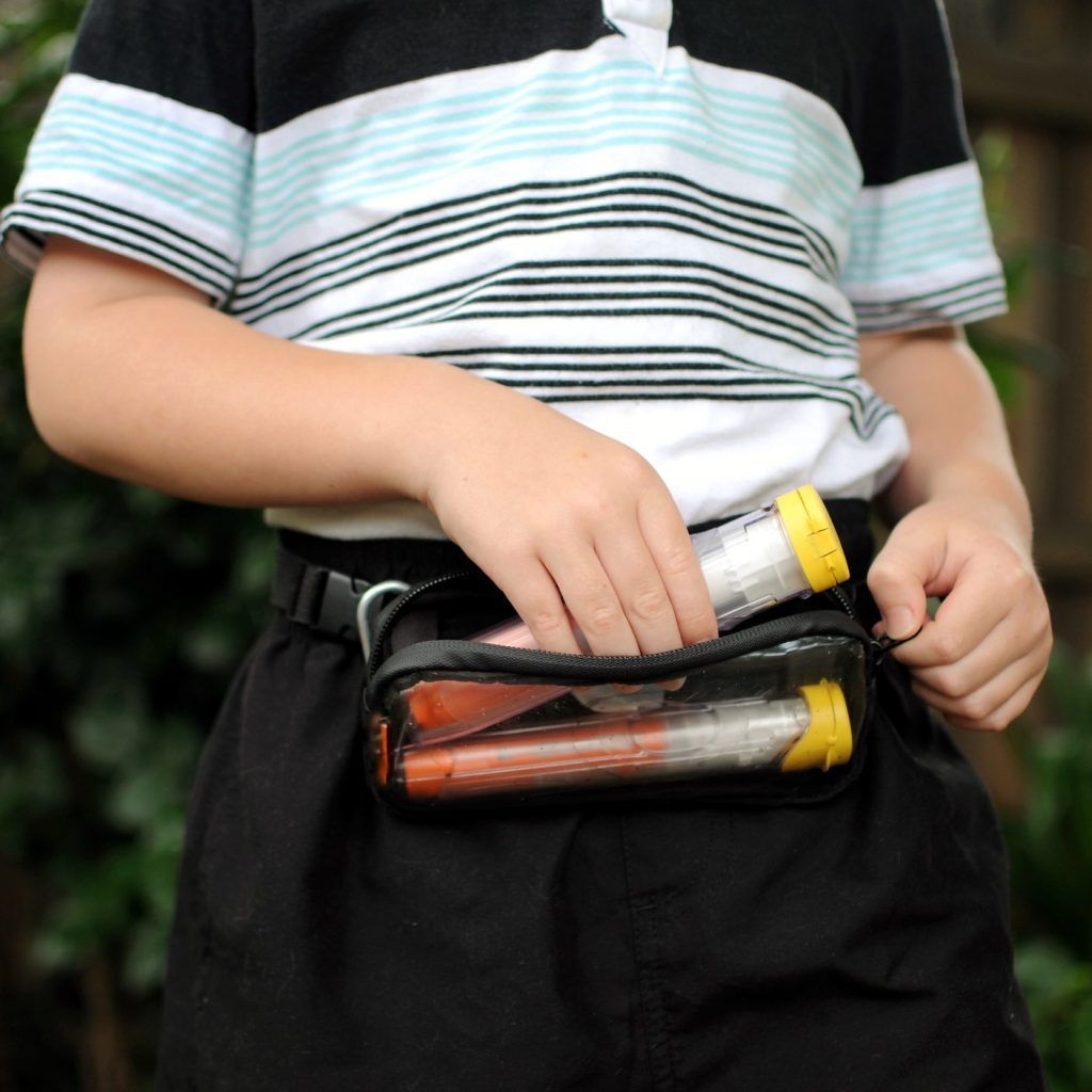 Boy wearing an auto-injector fanny pack, and taking on auto-injector out.