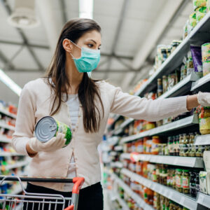 Woman shopping at grocery store wearing mask and gloves