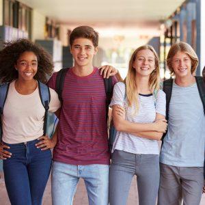 Groupe de quatre adolescents à l'école devant leus casiers