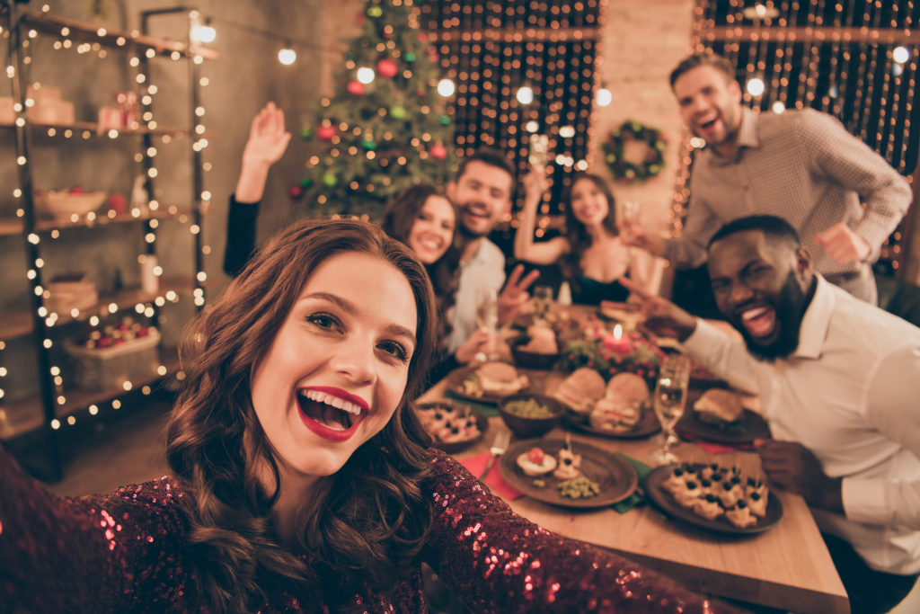 Close up photo of young adults around a table for a holiday party
