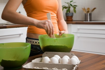 Teen girl mixing baking ingredients in a green bowl, with a carton of eggs on the table.