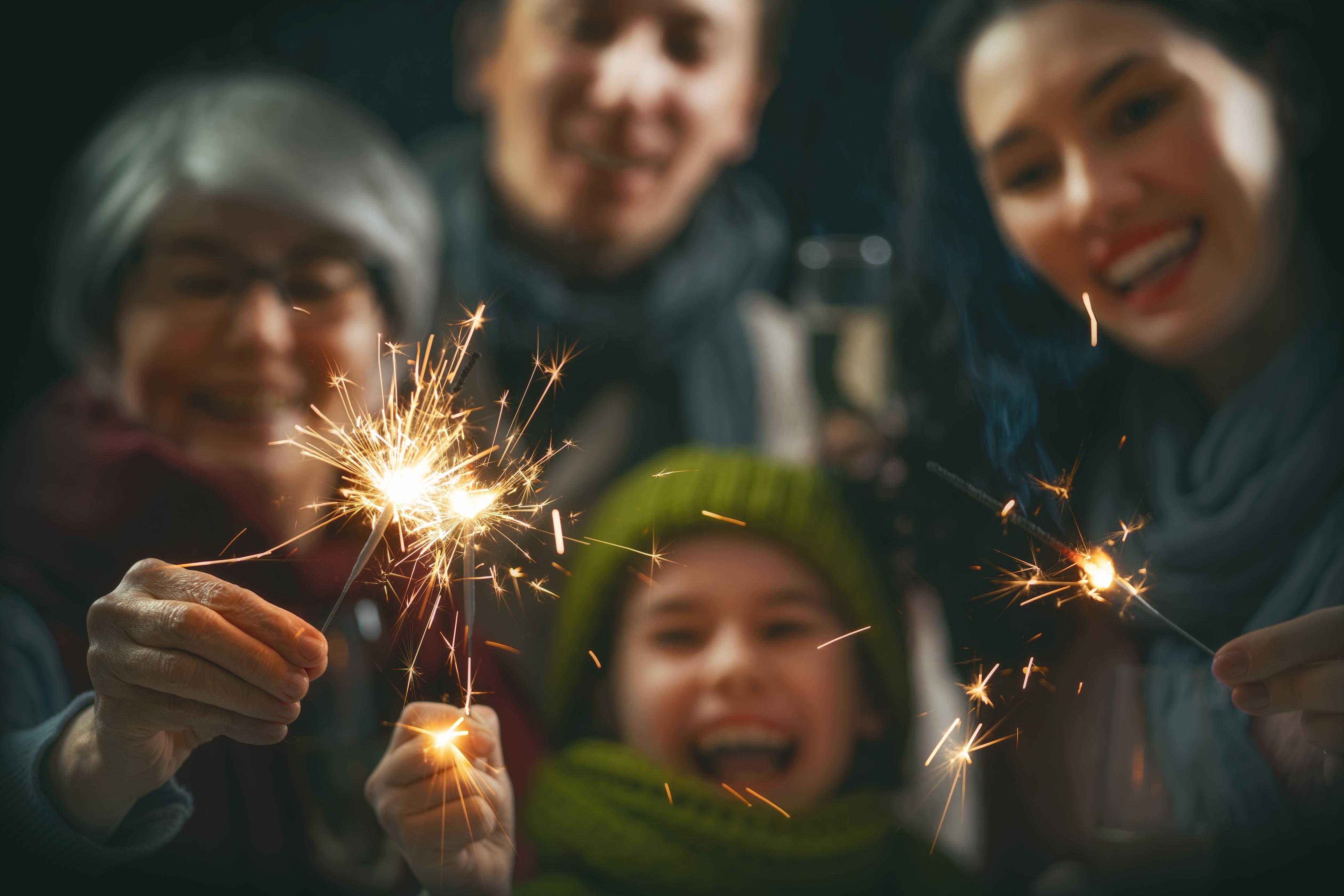Family having fun, holding sparklers.