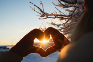 Heart shape symbol of the women mittens in winter frosty sunset. Concept of winter, dating, valentines day and love.