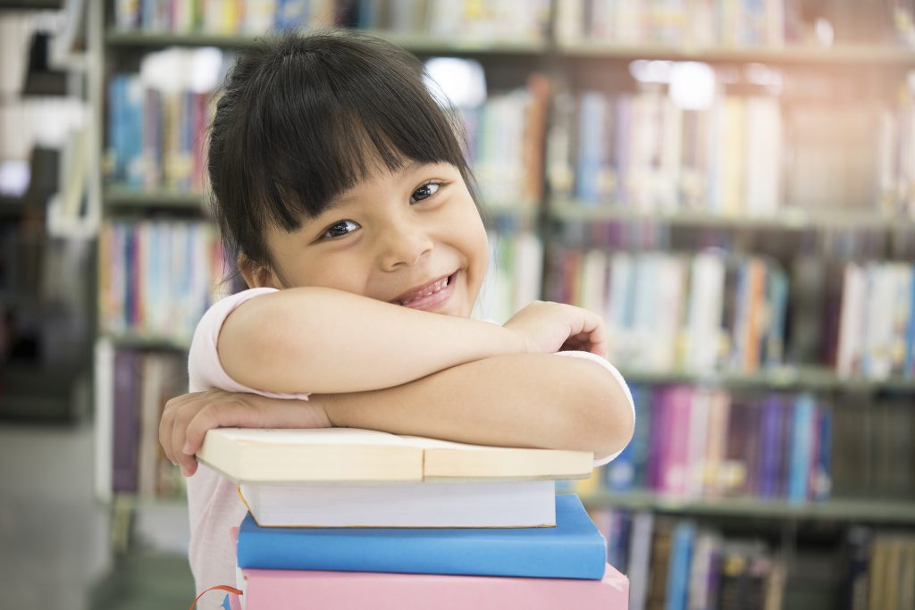 Girl smiling into the camera with her arms crossed across a stack of books.