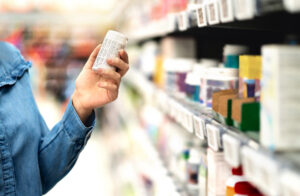Customer in pharmacy holding bottle. Woman reading the label text about ingredient information.