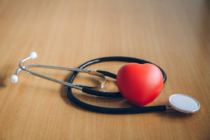 Black stethoscope and heart shaped stress ball on wooden table
