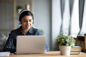 Millennial girl in headphones using laptop at home