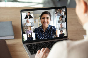 Laptop screen over woman shoulder view, videocall conversation.