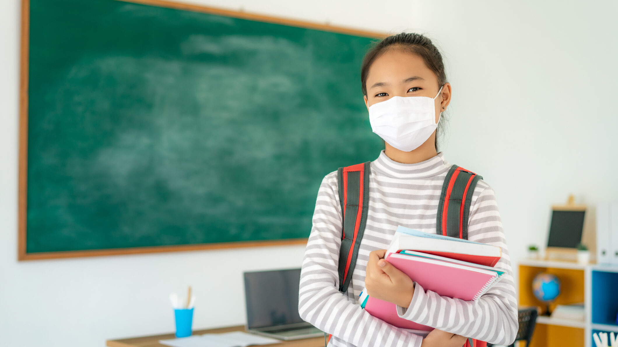 Asian primary students girl with backpack and books wearing masks to prevent the outbreak of Covid 19 in classroom while back to school reopen their school, New normal for education concept.