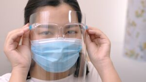 Young female who is wearing a face shield with mask rounded around her face from a frontal perspective to protect her glasses and eyes prepare to new normal. Coronavirus pandemic.