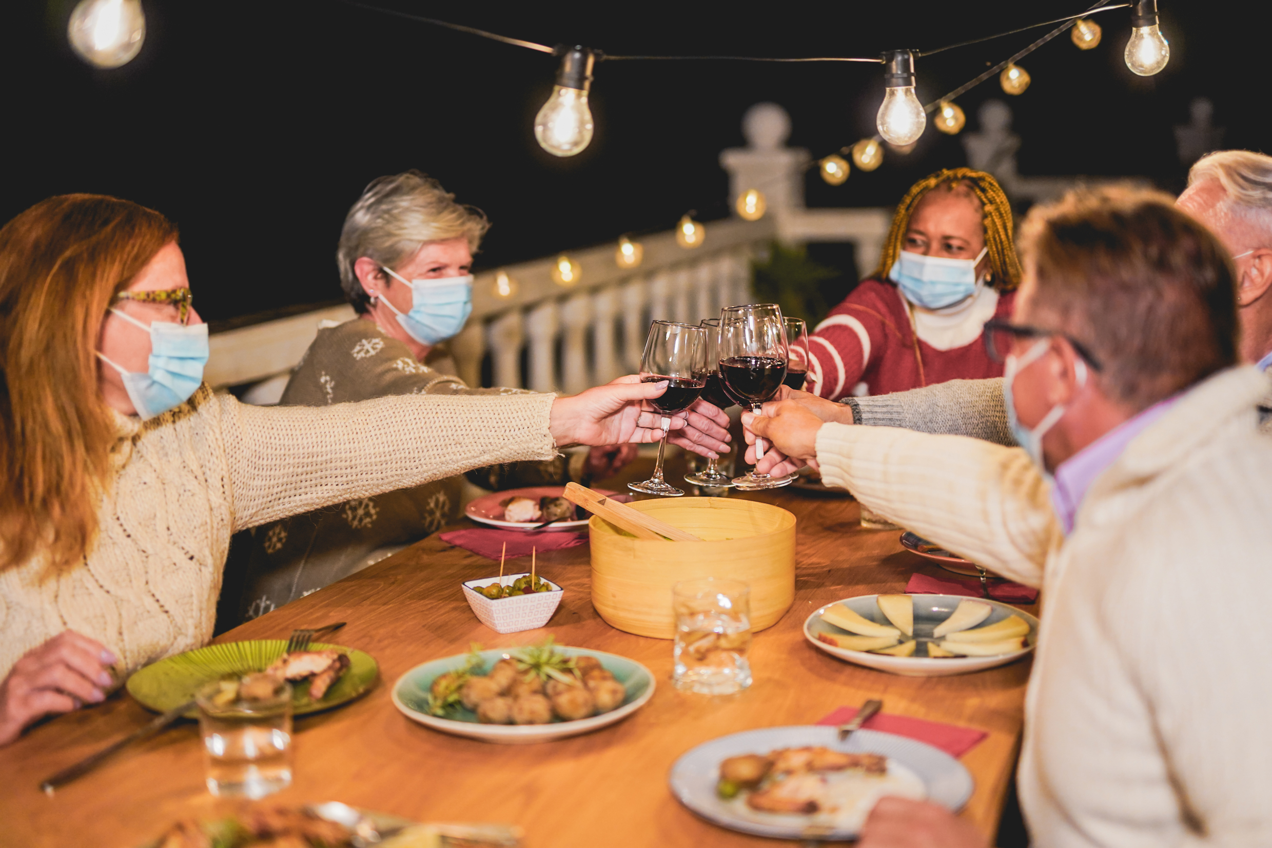 Happy multiracial senior people cheering with red wine at dinner while wearing surgical face mask for coronavirus