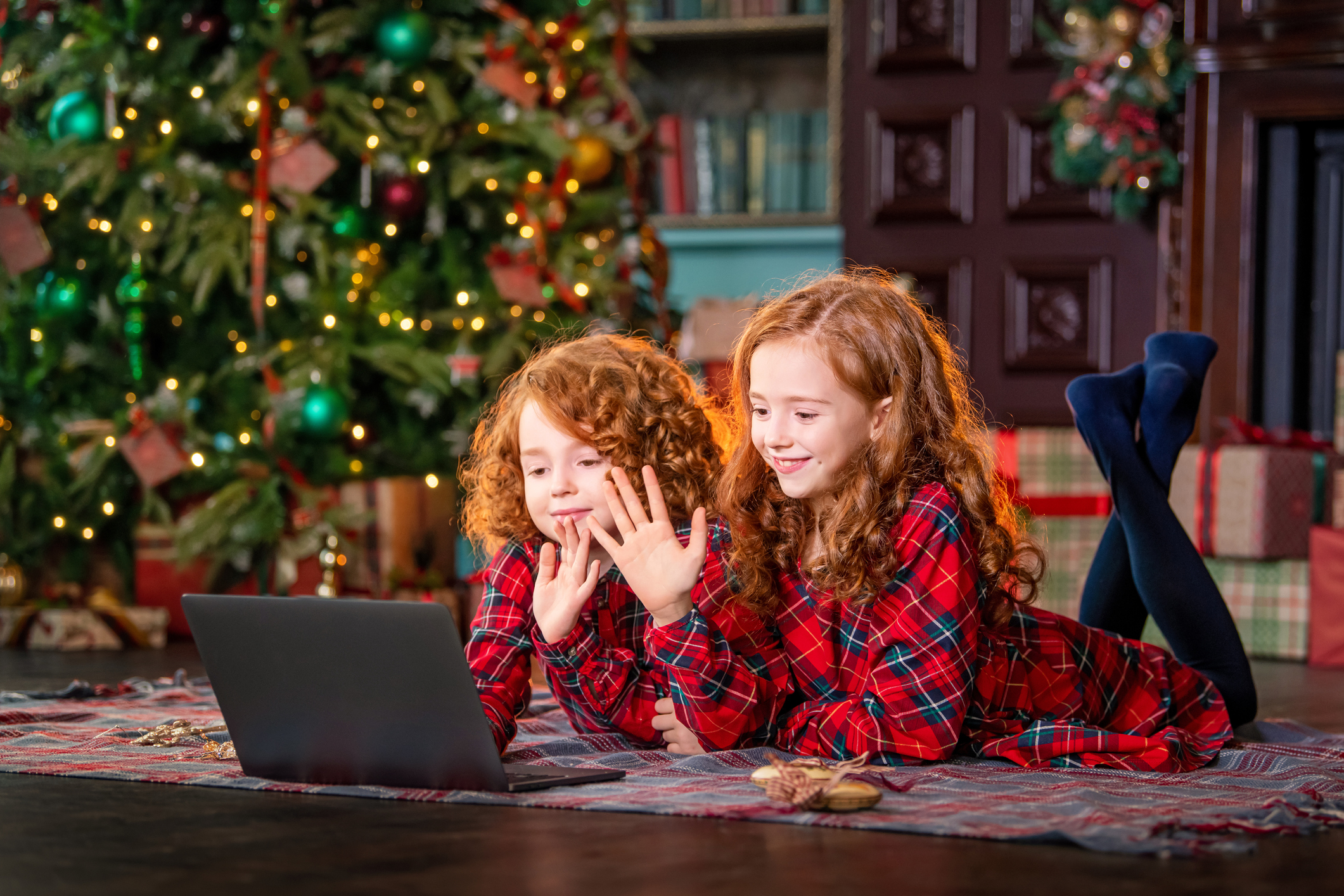 Red-haired children next to the Christmas tree and gifts communicate online through a laptop.