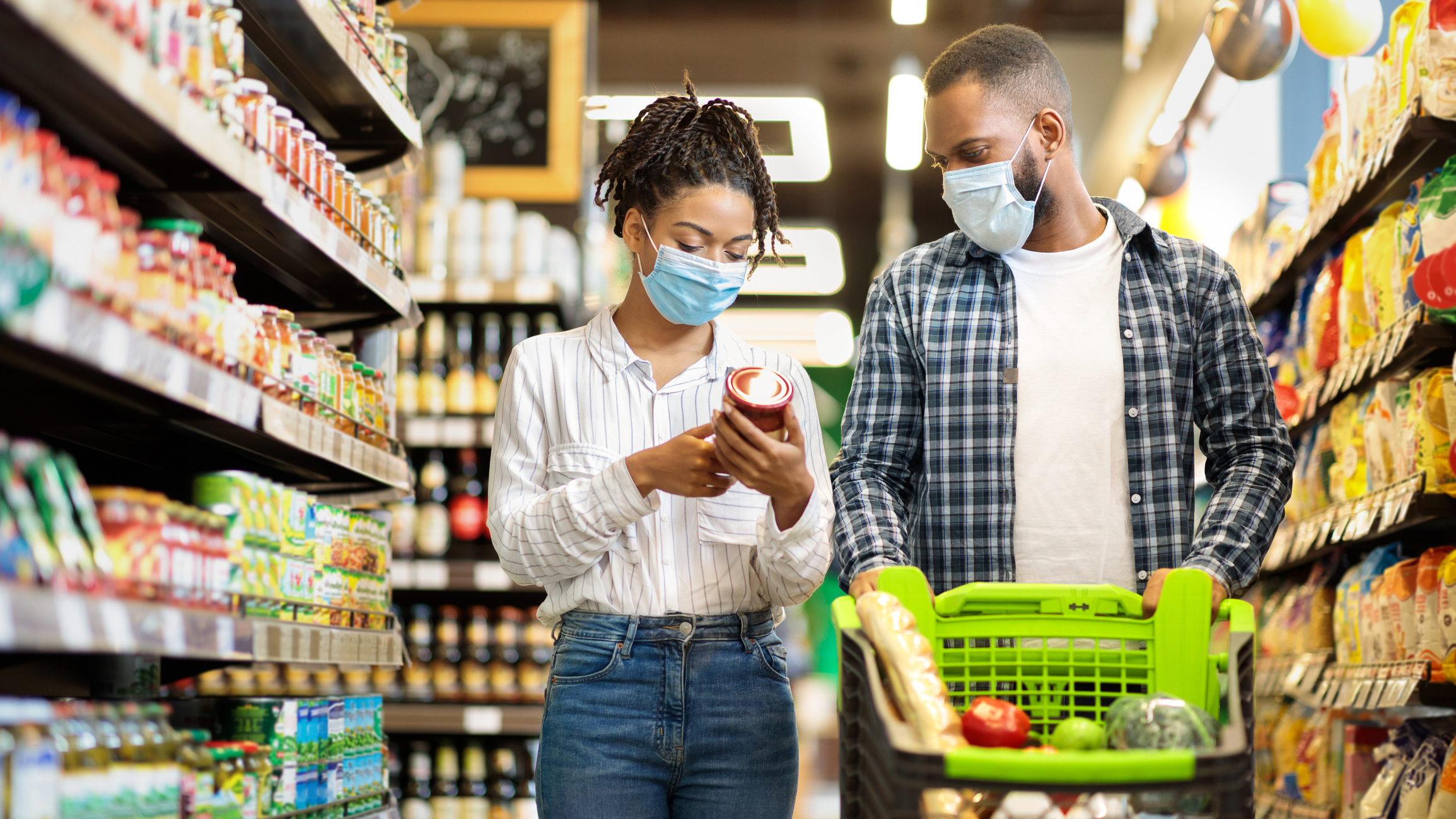 Couple In Shop Buying Groceries Wearing Face Mask
