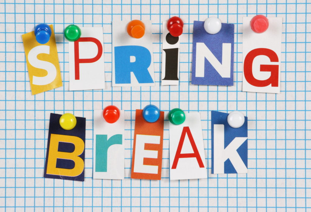 The words Spring Break in cut out magazine letters pinned to a background of blue graph paper