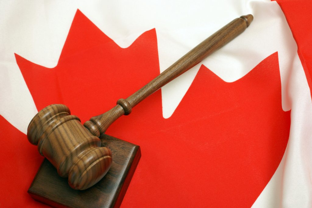 Wooden gavel resting on a block, atop a Canadian flag