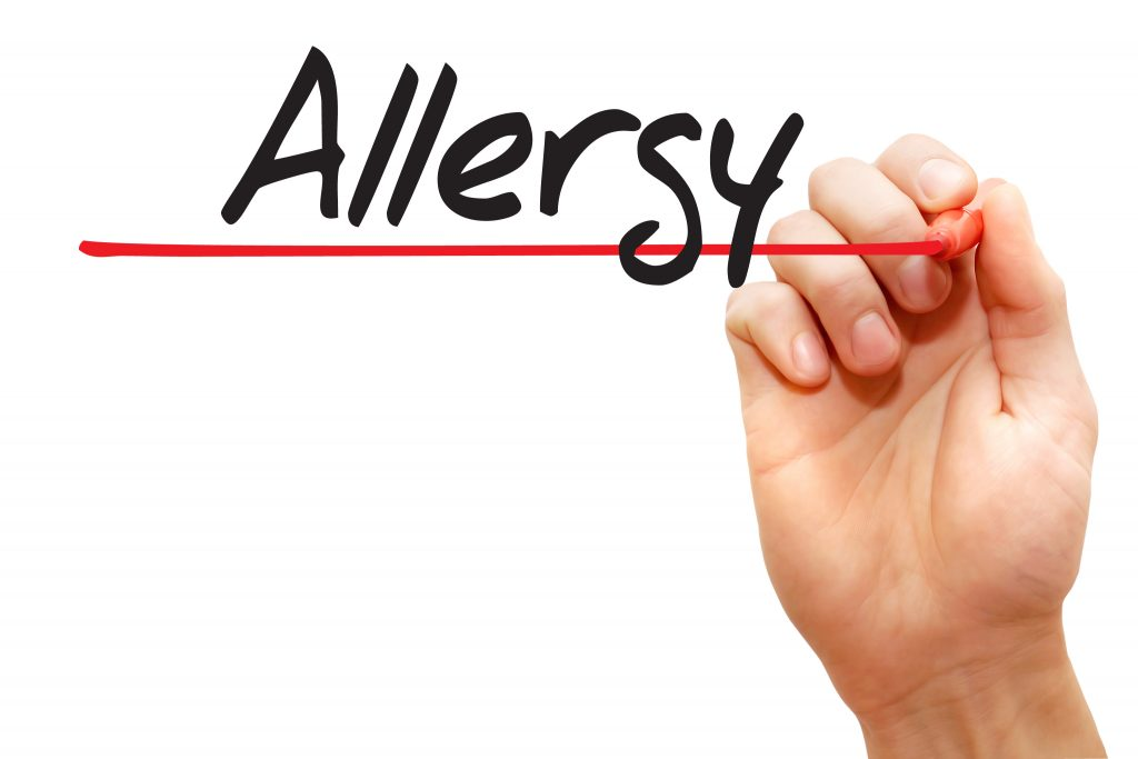 "Hand writing ""allergy"" on white board."