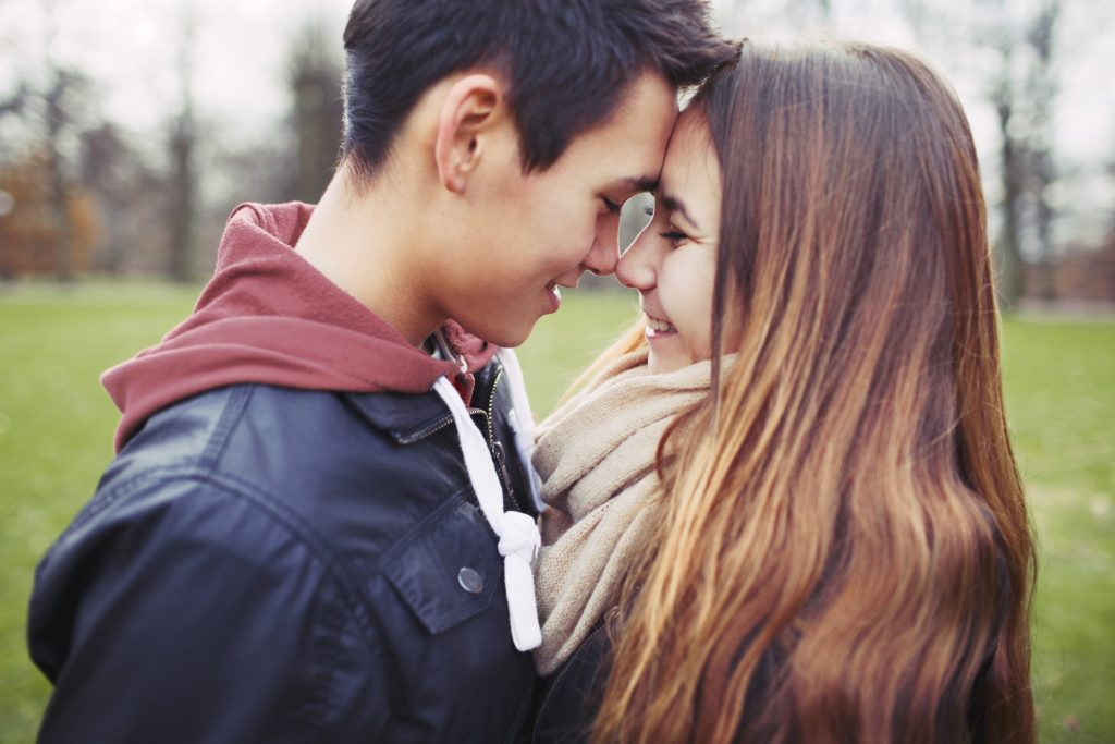 A male teen and a female teen in a close embrace with foreheads touching