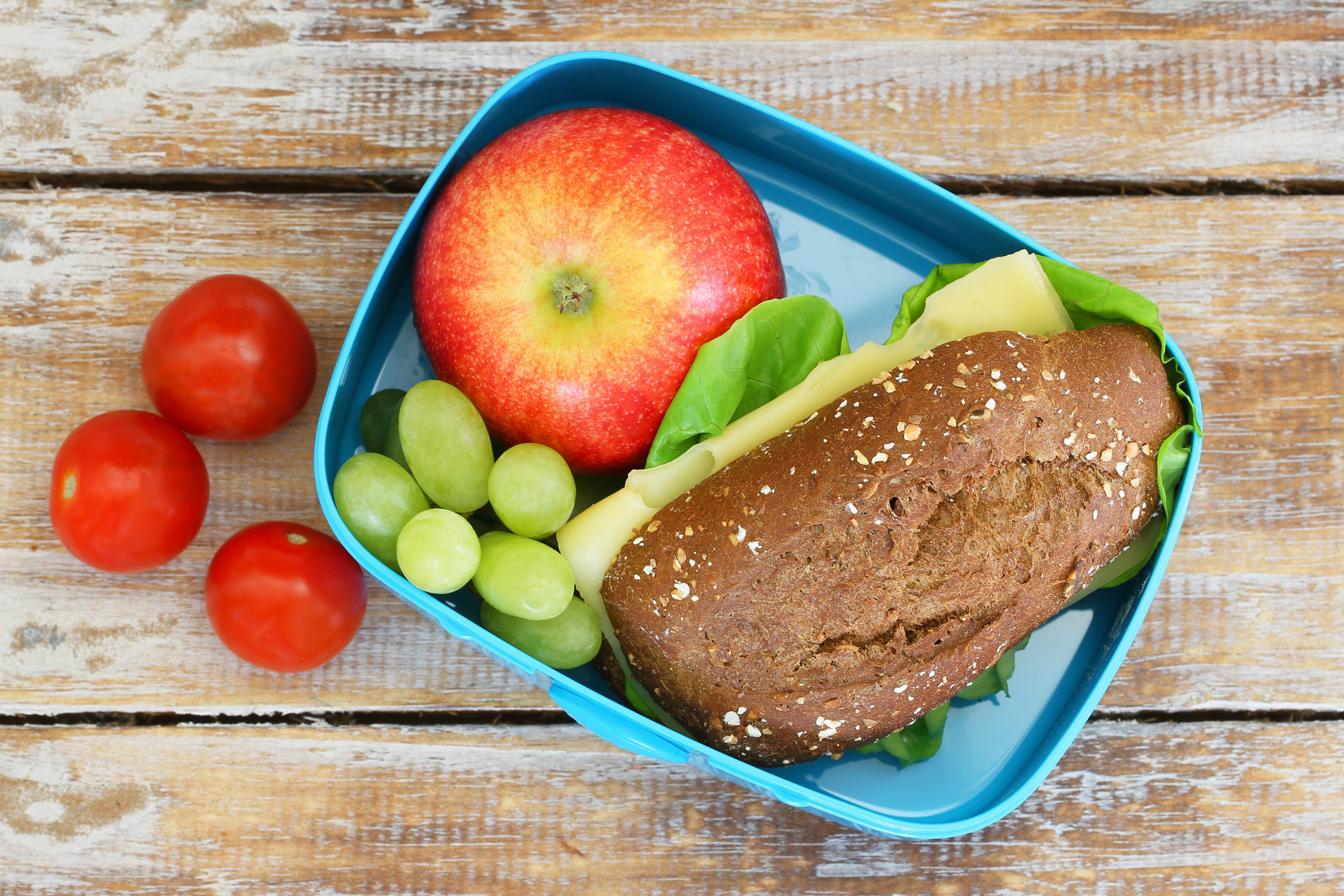 Lunch box consisting of wholegrain cheese sandwich, apple, grapes and cherry tomatoes
