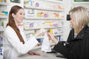 Pharmacist smiling as she hands customer a prescription bag