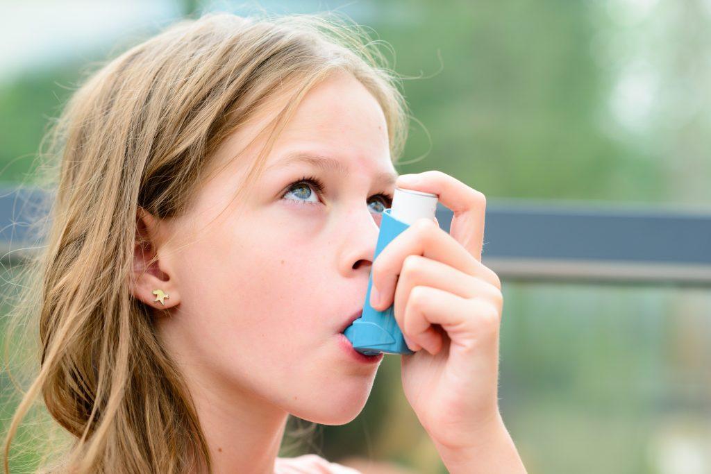 Jeune fille qui utilise son inhalateur contenant ses médicaments contre l'asthme.