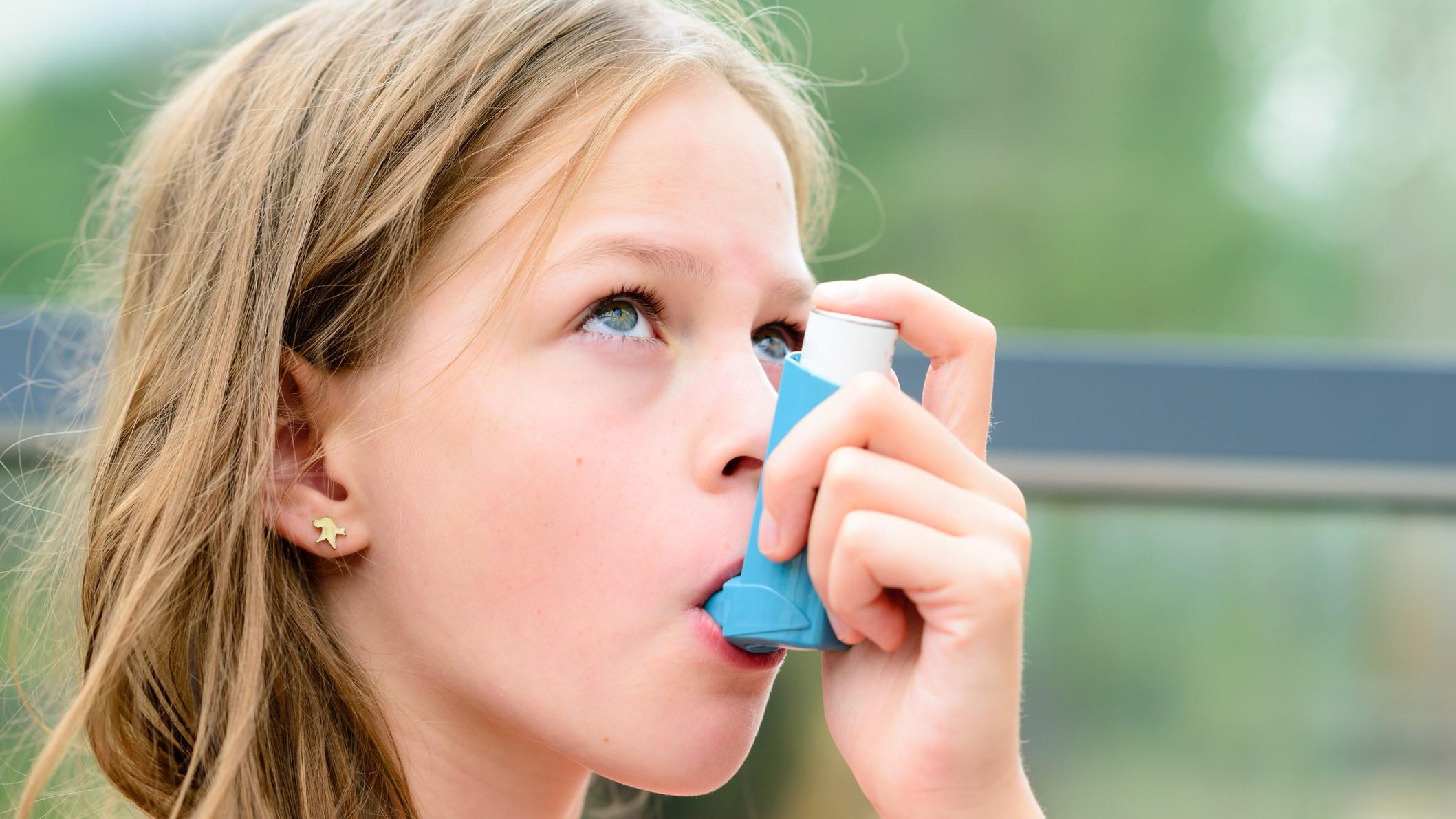 Pretty girl using asthma inhaler