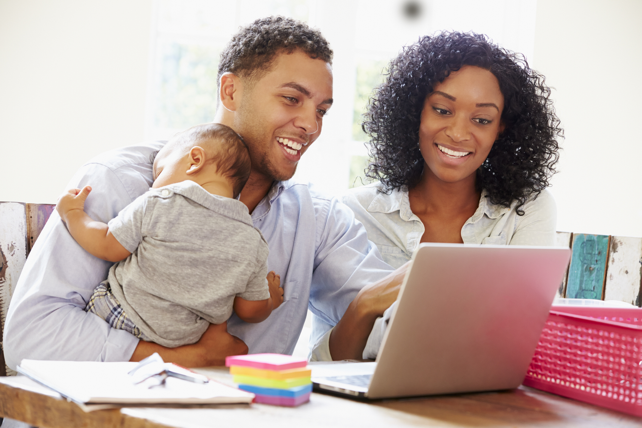 Parents With Baby Working In Office At Home Looking At Laptop Smiling