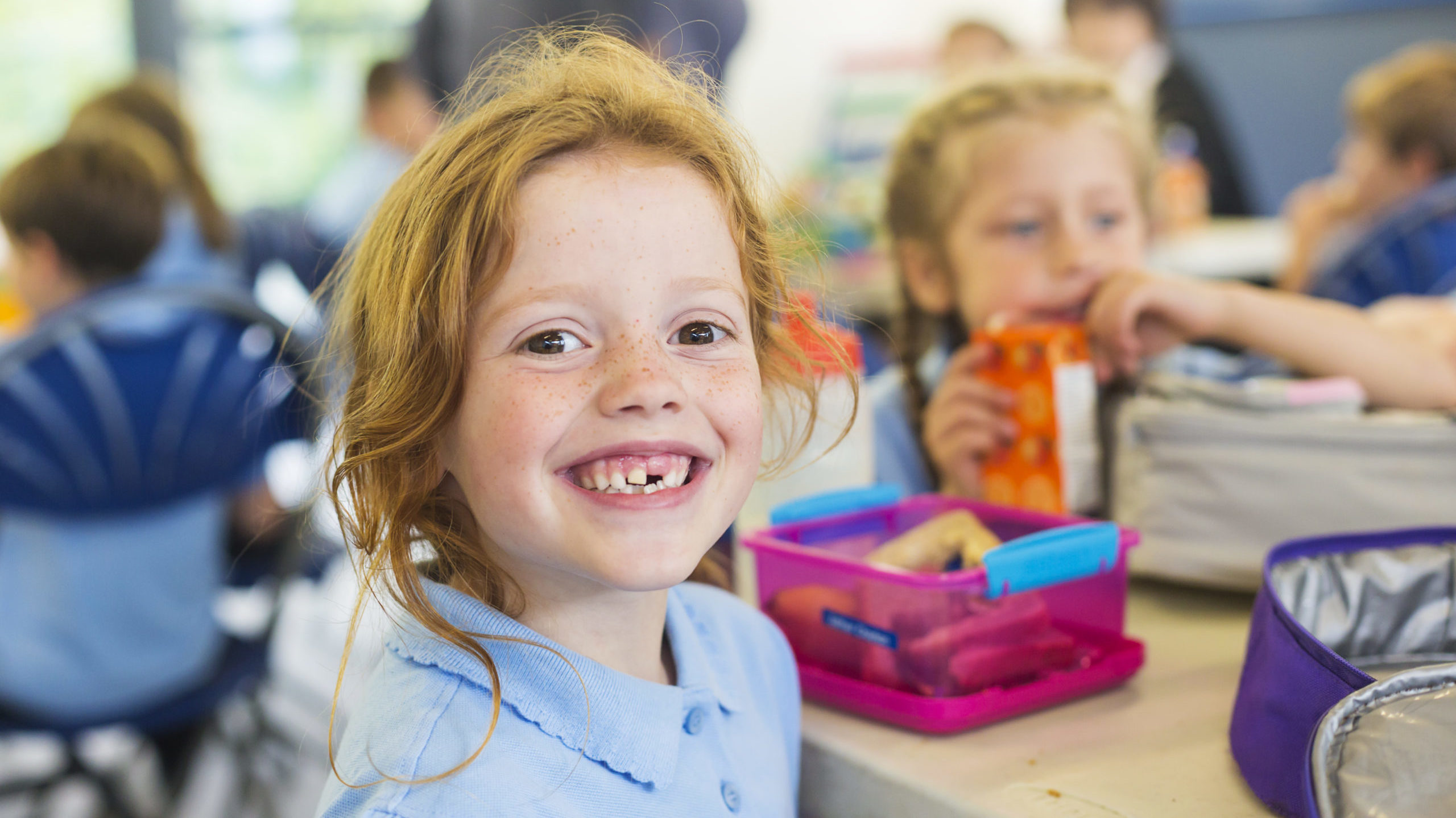 Smiling school students in uniform missing a tooth with a healthy sandwich for lunch