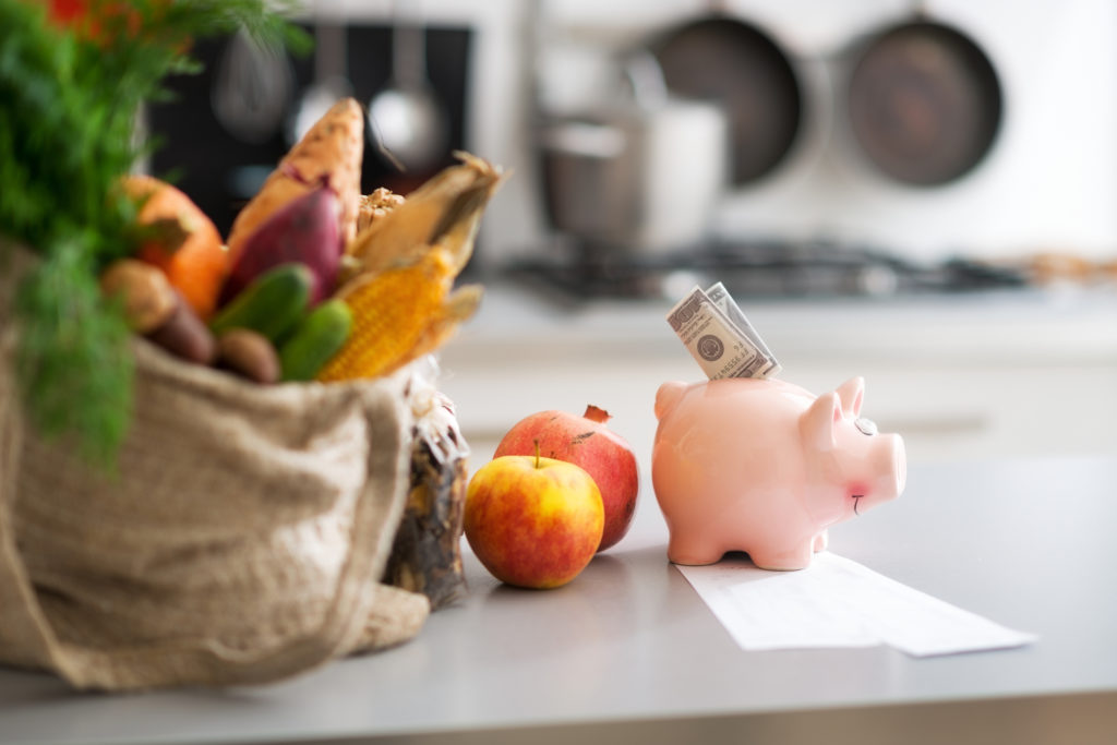 Money in piggy bank and grocery purchases on table. Closeup
