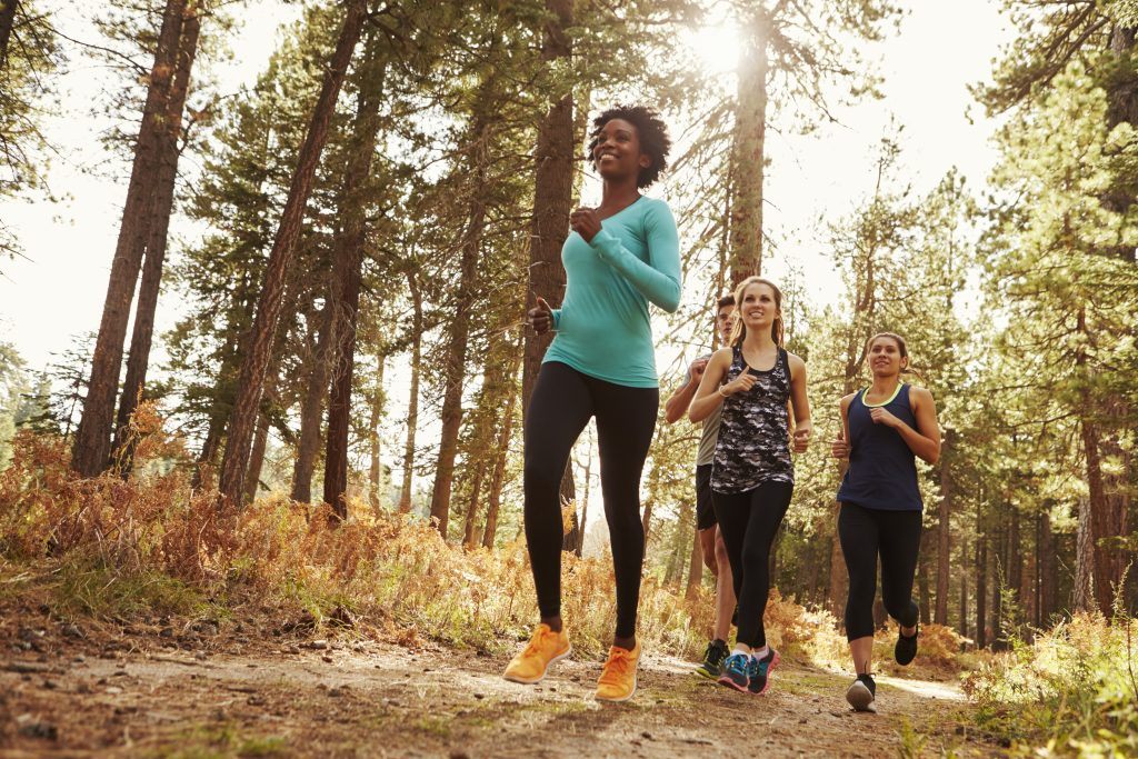 Three women jogging on a trail on a late summer day