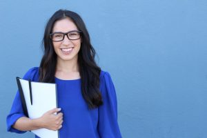 Graduate student holding a notebook smiling at camera