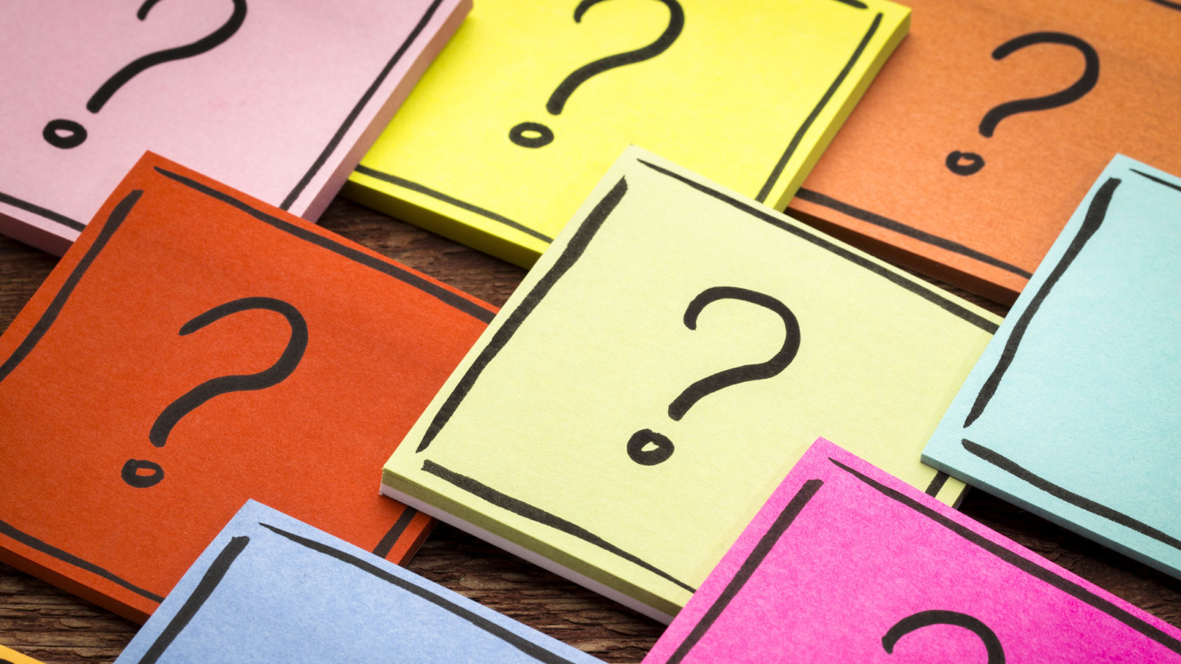 question mark concept - handwriting in black ink on colorful sticky otes against rustic wood