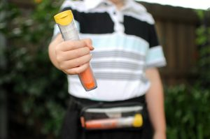 Boy holding an epinephrine auto-injector, and a second auto-injector is shown in a pouch that is across his waist.