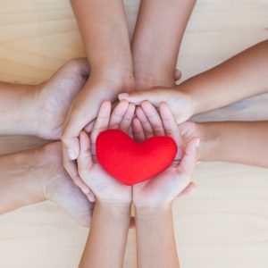 Family and friends stack hands with red heart showing unity, generosity, teamwork and love.