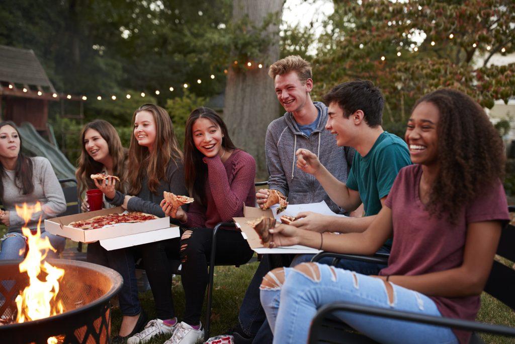 Groupe d'adolescents qui mangent de la pizza devant un feu de camp