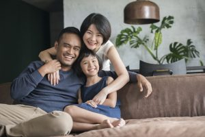 Young Asian parents with only child relaxing on the sofa in the living room.