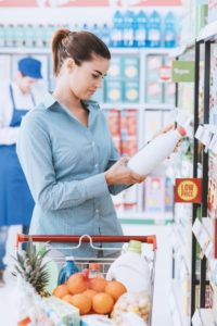 Woman reading ingredient label at grocery store.