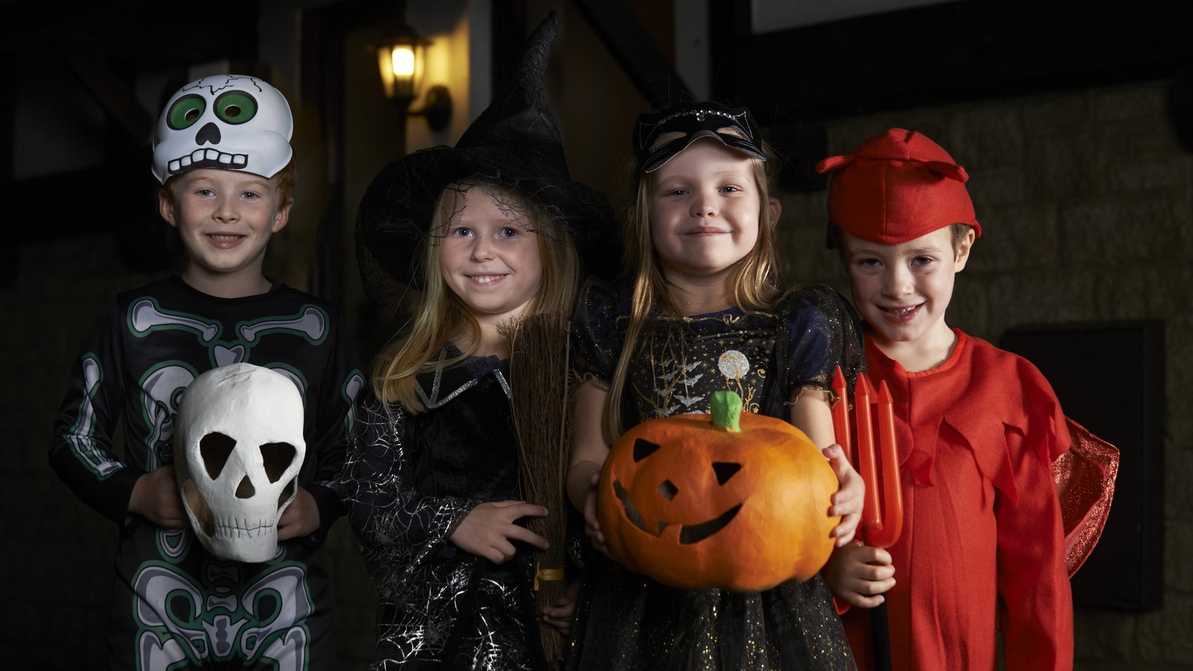 Halloween Party With Children Trick Or Treating In Costume